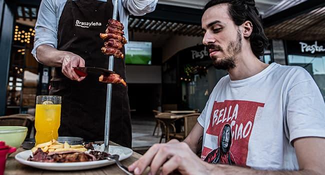 Hombre comiendo carne en Brasayleña